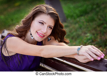 Young beautiful woman resting on a bench in the summer park.