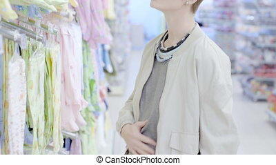 Happy pregnant woman choosing romper suit in supermarket