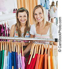 Bright female friends doing shopping smiling at the camera