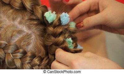 Hairdresser make braids in beauty salon.