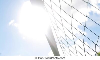 ball flying into football goal net - sport, soccer and game...