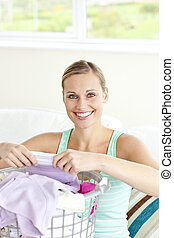 Cheerful young woman doing the laundry at home