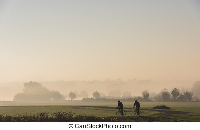 Two Cyclists in River Forelands - Morning with fog during...