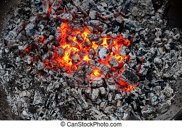 Fire and charred - Charred wood and bright flames on dark...