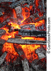 Fire background - Charred wood and bright flames on dark...