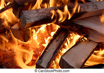 Flames and wood - Charred wood and bright flames on dark...