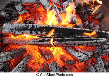 Flames on wood - Charred wood and bright flames on dark...