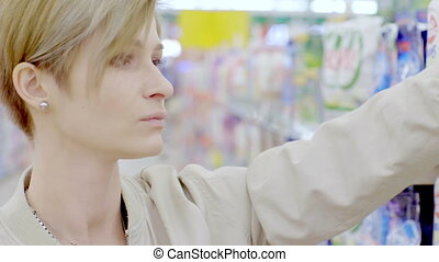 Woman choosing cleanser in supermarket - Young woman...