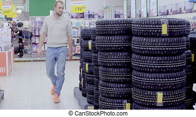 Man choosing winter tires in supermarket - Young man...