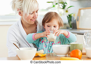 Radiant woman having breakfast with her daughter in kitchen