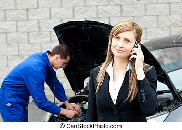 Man repairing car of business woman - Man repairing black...