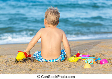 Cute boy on the tropical beach playing toys