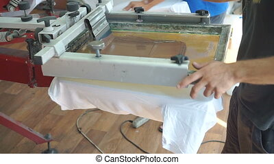 Screen printing manufacturing on t-shirts. Worker print an...