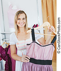 Bright caucasian woman holding a dress smiling at the camera...