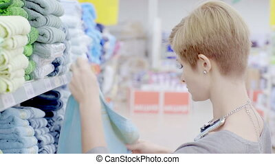 Woman choosing towels in supermarket - Young woman choosing...