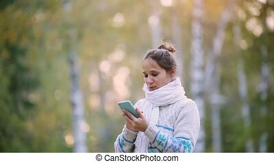 Smiling woman in a knitted sweater and scarf using mobile...