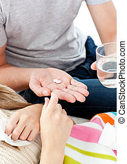 Close-up of young man giving pills to his morbid girlfriend