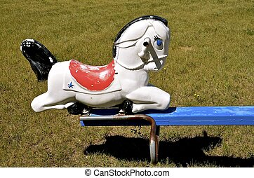 Plastic horse on a teeter totter - An old plastic horse...
