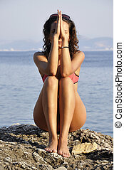 dark-haired girl sitting on  the beach