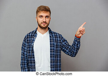 Portrait of a smiling man pointing finger up