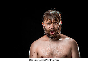 The water splash on male face and  against black background