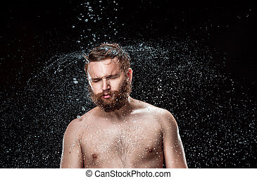 The water splash on male face and torso against black...