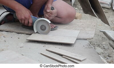 Worker cutting tile saw blade outside