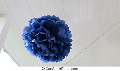 blue ball of paper spinning around its axis on white ceiling