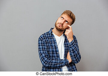 Portrait of a casual pensive man standing and looking away -...