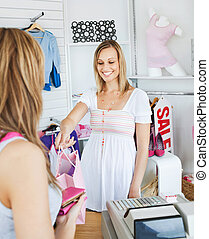 Smiling saleswoman giving clothes to a female customer in a...