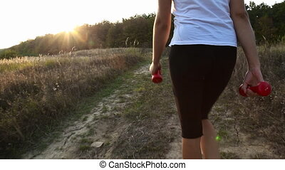 woman with dumbbells goes on a dirt road
