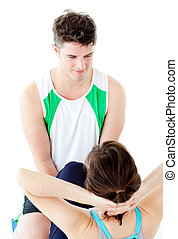 Attractive man doing fitness exercises with a woman in gym