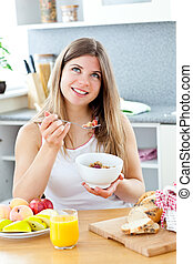 Glowing brunette woman eating cereals with raspberries...