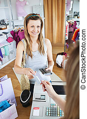 Charming young woman buying clothes with her card in a shop