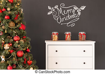 Decorated Christmas tree and white dresser standing beside...