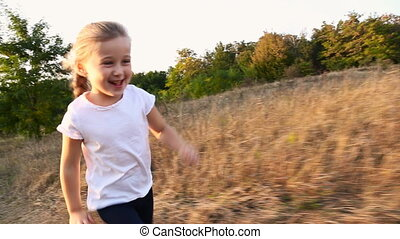little girl quickly runs on a dirt road