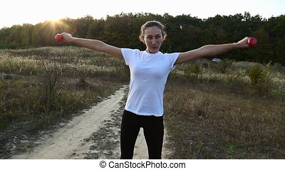 Woman trains with dumbbells in nature