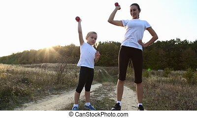 Mom with her daughter raise the dumbbells