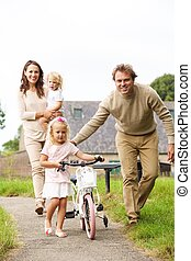 Happy young family walking in the park with a small bicycle