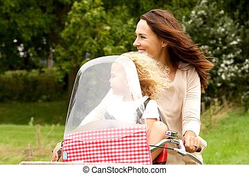 Mother and daughter riding on bicycle in the park - Portrait...