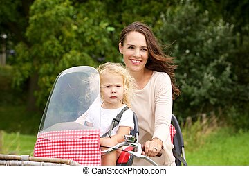 Mother taking her daughter on bicycle ride in the park