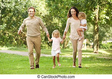 Happy young family of four walking in the park