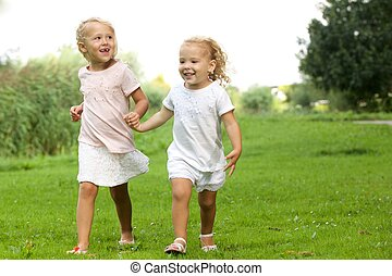 Two little girls walking in the park