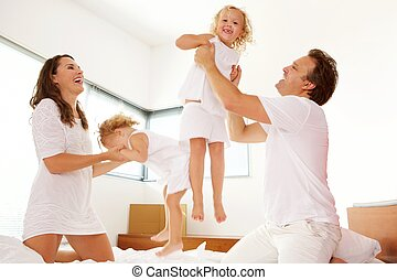 Happy young family playing in the bedroom - Portrait of...