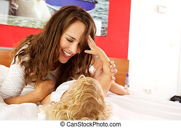 Loving mother playing with daughter on bed