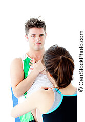 Muscular man doing fitness exercises with a woman