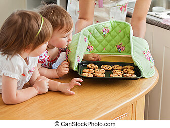 Smiling woman baking with her daughters in kitchen