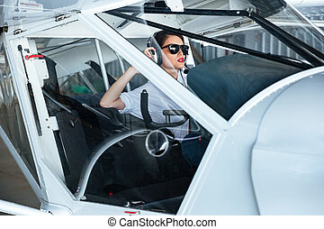 Beautiful young woman pilot sitting in cabin of small...