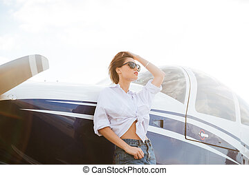Woman in sunglasses standing outdoors near small private...