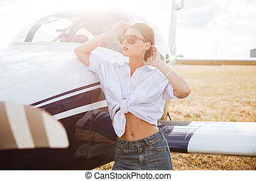 Woman in sunglasses standing outdoors near small plane -...